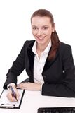Positive bank official. Young woman sitting at the table Royalty Free Stock Images