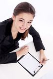 Positive bank official. Young woman sitting at the table Royalty Free Stock Photos