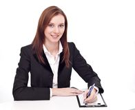 Positive bank official. Young woman sitting at the table Stock Image
