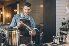 Positive bartender looking at the cocktail shaker. Cheerful young man standing at the bar counter and smiling while using a cocktail shaker royalty free stock photos
