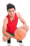 Positive basketball player. Portrait of a teenage boy with basketball looking at camera and smiling Royalty Free Stock Images