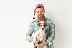 Positive bearded male model wears festive hat and checkered shirt, holds his favourite pet, over white stock photos
