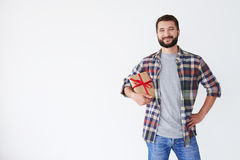 Positive bearded man holding present box under his arm Stock Photography