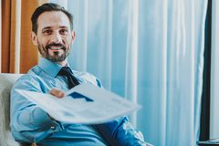 Positive bearded man offering the documents and smiling royalty free stock image