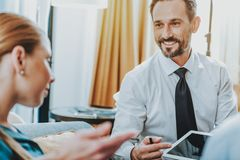 Positive bearded man smiling and showing tablet to woman royalty free stock image