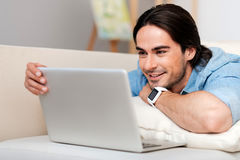 Positive bearded man using laptop. Time for rest. Cheerful smiling handsome man using laptop and expressing gladness while resting on the couch royalty free stock photo