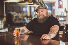 Positive bearded obese male drinking beverage in bar Stock Photo