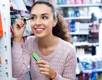 Positive beautiful female customer buying mascara Royalty Free Stock Image