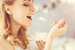 Positive beautiful woman eatign yoghurt. One more spoon. Positive delighetd woman eating joghurt and expressing joy while smiling Stock Images
