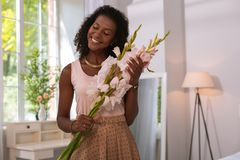 Positive beautiful woman holding flowers at home. Beautiful bouquet. Positive nice woman holding flowers while standing in the room stock photos