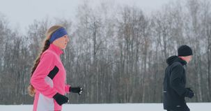 Young man and woman on a morning run in the winter forest. A woman in a loose jacket a man in a black jacket is running stock video footage