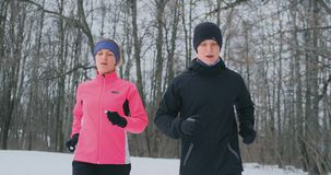 Young man and woman on a morning run in the winter forest. A woman in a loose jacket a man in a black jacket is running stock footage
