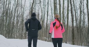 Positive beautiful young healthy couple running with sportswear through the forest in the sunny winter morning. the view stock video