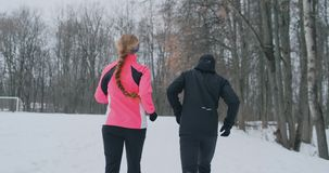 Positive beautiful young healthy couple running with sportswear through the forest in the winter morning stock video footage