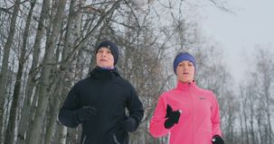 Positive beautiful young healthy couple running with sportswear through the forest in the winter morning stock footage