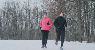 Positive beautiful young healthy couple running with sportswear through the forest in the winter morning stock video