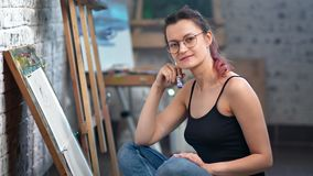Positive beautiful young painter woman posing at art studio during working medium shot. Portrait of charming female artist holding paintbrush relaxing enjoying stock video