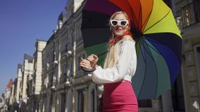 Pretty young woman looking at the camera holding multicolored umbrella standing on the street. Attractive fashionable. Positive beautiful young woman looking at stock video footage