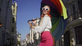Positive beautiful young woman looking at the camera holding multicolored umbrella on the street. Attractive fashionable. Girl enjoying sunny day in old stock footage