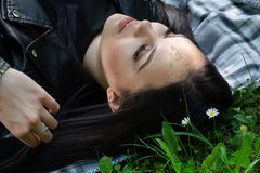 A positive woman lying down on a blanket in the meadow on spring sunny day and looking up royalty free stock photo