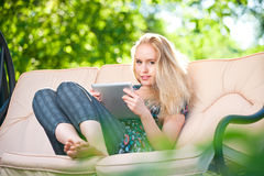 Positive beautiful young woman using tablet Stock Images