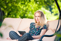 Positive beautiful young woman using tablet Royalty Free Stock Image