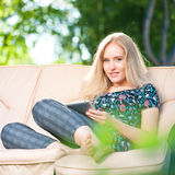 Positive beautiful young woman using tablet Royalty Free Stock Photography
