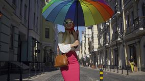 Positive beautiful young woman walking on the street, turning and looking at the camera holding multicolored umbrella. Positive beautiful young woman walking on stock video