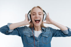 Positive begeisterte blonde hörende Musik Lizenzfreies Stockfoto