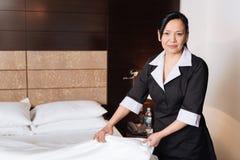 Positive begeisterte Frau, die im Hotelzimmer steht stockfotografie