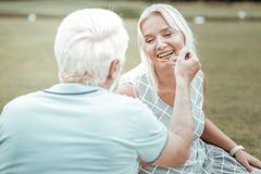 Positive begeisterte Frau im Ruhestand, die Lächeln auf Gesicht hält stockbild