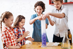 Positive begeisterte Jungen, die einige chemische Reagenzien zu einer Retorte setzen lizenzfreie stockfotos