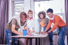 Positive begeisterte Mitschüler, die ihre Hauptaufgabe vorbereiten stockbild