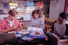 Positive begeisterte Mitschüler, die zusammen in der Kantine studieren lizenzfreie stockbilder