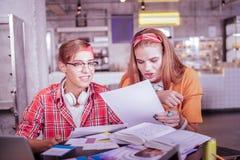 Positive begeisterte Mitschüler, die zusammen ihre Aufgabe lesen lizenzfreie stockbilder