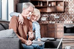 Positive begeisterte Paare, die entlang des Computers anstarren stockfoto