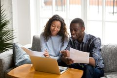 Positive black couple with bills and laptop at home. African black positive married couple sitting on sofa at home read documents paper checking bills, bank stock images