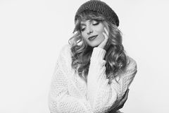 Positive blond woman in sweater and hat isolated on white backgr Royalty Free Stock Images