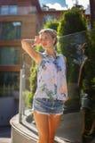 Positive blonde Frau in den Denimkurzen hosen Lizenzfreie Stockfotos