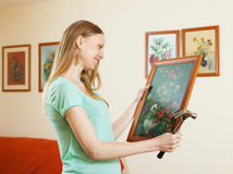 Positive blonde girl hanging  pictures Royalty Free Stock Photos