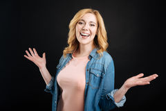 Positive blonde girl holding hands bent in elbows. I am here. Beautiful smiling woman wearing jeans shirt on pink T-shirt keeping arms in the air looking Stock Photo