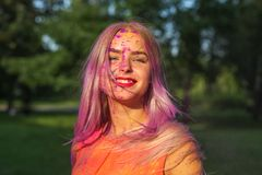 Positive blonde girl with long hair covered purple dry paint celebrating Holi festival. Positive blonde woman with long hair covered purple dry paint celebrating stock photos