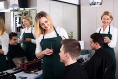 Positive blonde hairdresser serving teenager Stock Image