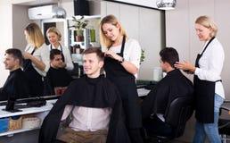 Positive blonde hairdresser serving teenager Royalty Free Stock Photo