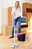 Positive blonde housewife washing parquet floor Royalty Free Stock Photography