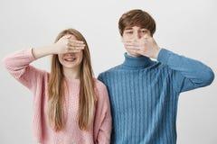 Positive blonde kaukasische Paare Mann in der blauen Strickjacke versteckt Mund hinter Palme, doesn t möchten Geheimnis teilen, w Lizenzfreie Stockfotografie