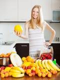 Positive blonde langhaarige Frau mit Melone Stockbilder
