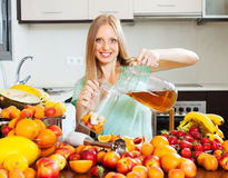 Positive blonde long-haired girl making fresh beverages Stock Images