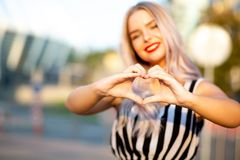 Positive blonde model with red lips making heart sign with her fingers at the street. Space for text stock photography