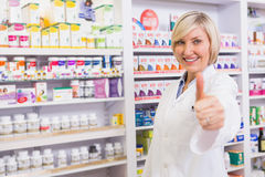 Positive blonde pharmacist with thumb up Stock Image